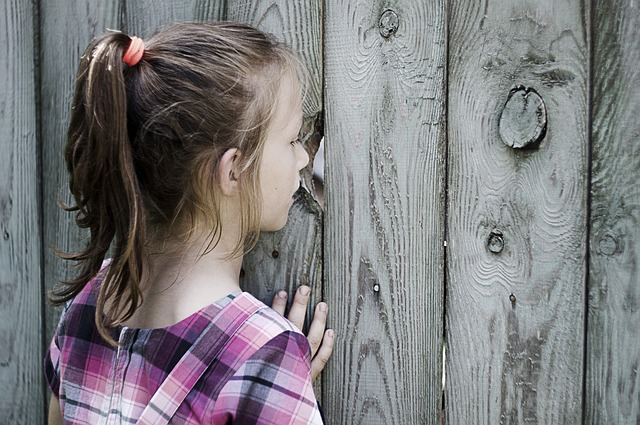 Young girl looking through a hole in the wooden fence